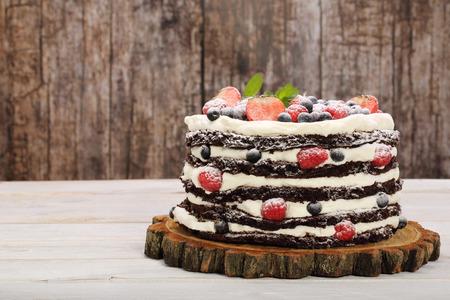 postre: pastel de chocolate con crema blanca y frutas frescas con el espacio para el texto Foto de archivo