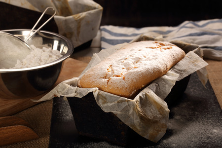 Homemade pound cake with powdered sugar in baking mold Archivio Fotografico