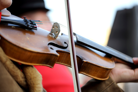 fiddles: Musician playing violin on the street. Close up photo.