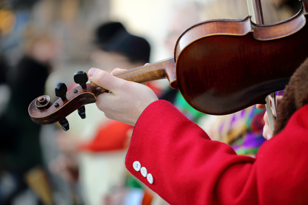 solo violinist: Musician playing violin on the street. Close up photo.