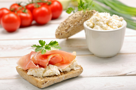 meat diet: Sandwich with white cottage cheese and ham on white wooden background