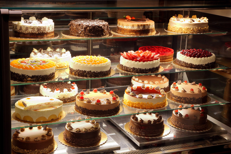 Different types of cakes in pastry shop glass display Stockfoto