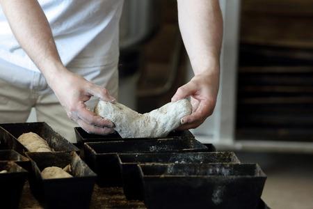빵 굽는 사람은 빵 반죽을 형에 넣습니다.