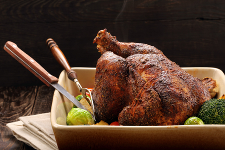 Whole roast chicken with vegetables in bowl on wooden background Standard-Bild