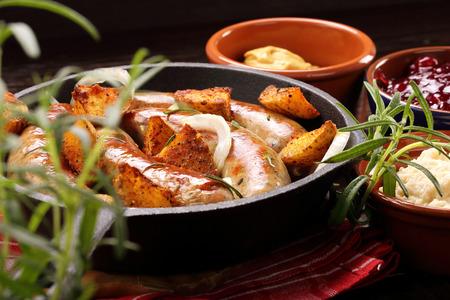 saucisse: saucisses blanches avec des pommes de terre cuites au four dans une po�le � frire Banque d'images