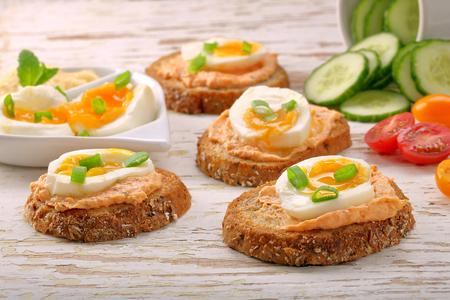 연어 붙여 넣기와 흰색 나무 배경에 달걀 샌드위치