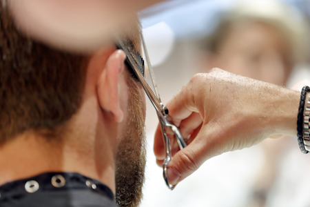 trimming: Hairdresser trimming hair with scissors Stock Photo