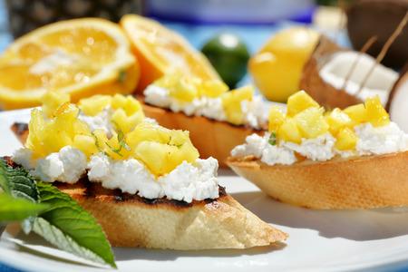 queso fresco blanco: tosts con requesón y piña en un plato