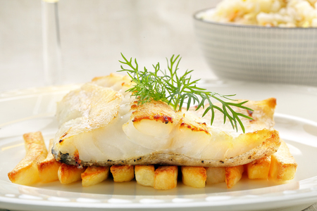 Baked fish and chips on white plate Stock Photo