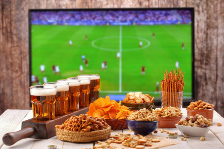 Beer and snacks set football match on tv background