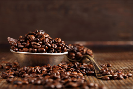 space for text: Coffee beans in a bowl on brown vintage background with space for text Stock Photo