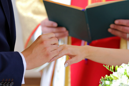Bride and groom during wedding rings exchange at the church Stock Photo