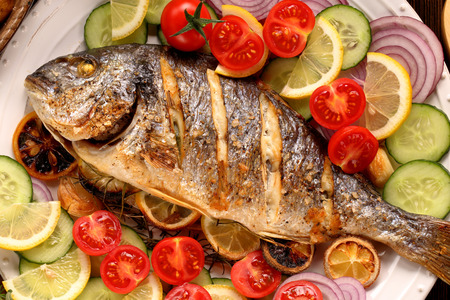 Grilled fish and vegetables on the plate