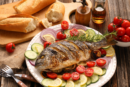 Grilled fish with baguette and vegetables on the plate