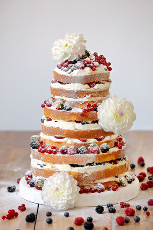 Wedding rustic naked cake with flowers on wooden background