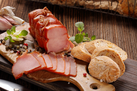 Fresh ham and bread on wooden background