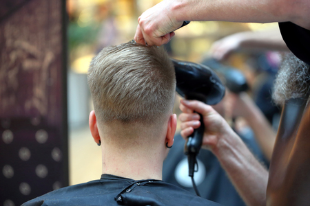secador de pelo: Hairdresser makes hairstyle with hair dryer in barbershop