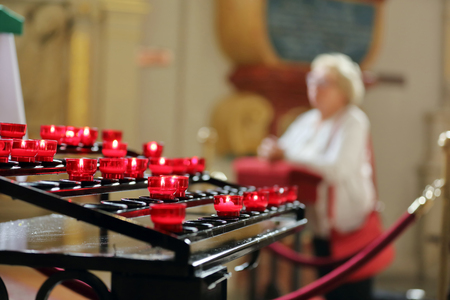 Old woman praying in a church on the knees and place for text