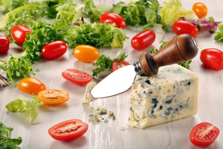 stilton: Blue cheese with tomato on stone background and space for text