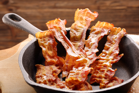 Hot fried bacon pieces in a cast iron skillet
