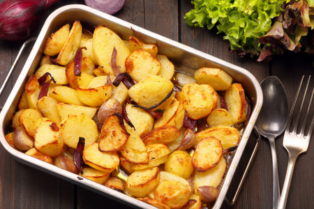 roasting pan: Baked potatoes in a roasting pan with garlic and onion on a wooden background