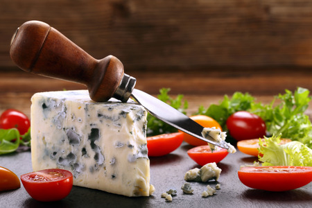 stilton: Blue cheese with tomato on wooden background and space for text