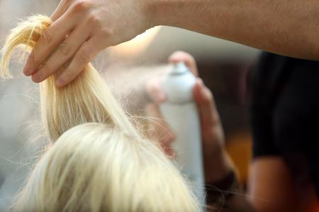 Hairdresser arranging hairdo using hairspray   Stock Photo