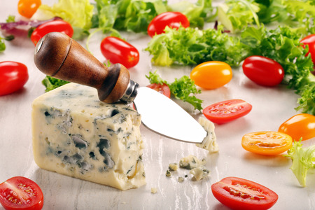 stilton: Blue cheese piece with tomato on stone background and space for text