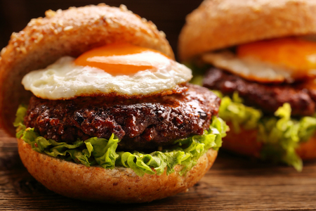Hamburger with beef meat and egg on wooden background