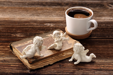 cherubs: Old book, the three angels and cup of coffee with empty spase for text