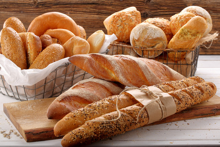 Different types of breads on wooden background with empty space for text