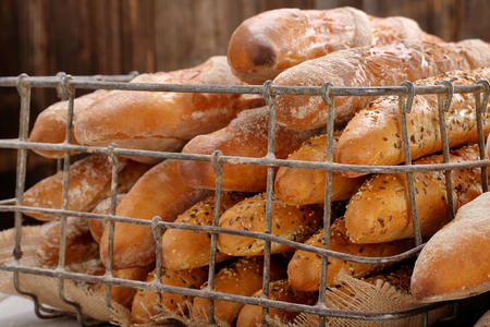 Different types of baguettes in metal basket in bakery  Stock Photo