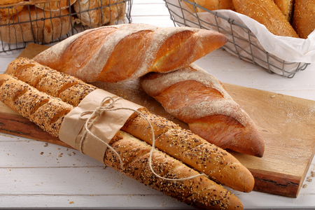 Fresh baguettes in bakery on wooden background   Stock Photo
