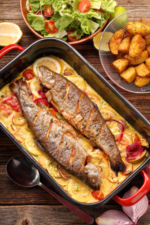 brown trout: Baked trout with lemon sauce and vegetables in a pan Stock Photo