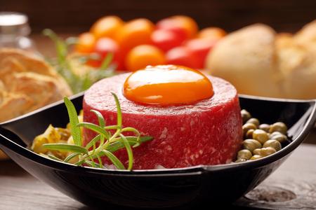 tatare de carne con huevo, cebolla, pepino y alcaparras