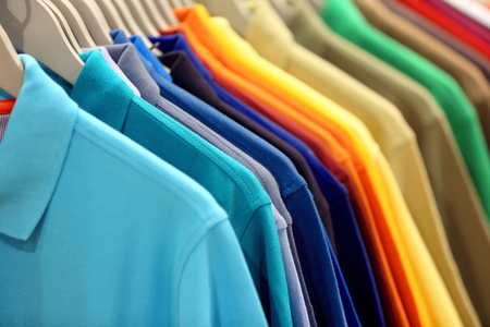 Row of men's polo shirts in wardrobe or store with empty space for text Foto de archivo