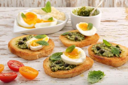 Sándwich fresco con pesto y huevo sobre fondo de madera