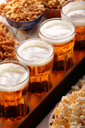 Beer row and snacks on wooden background football fan set