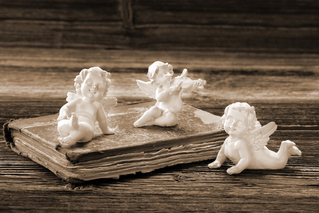 The old book and the three angels with empty space for text   Stock Photo