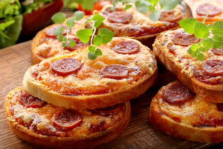 Fresh toast with cheese and chorizo sausage on wooden background