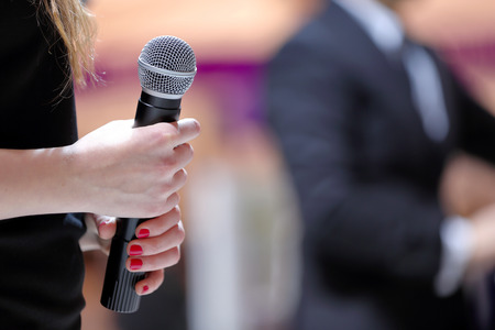 Woman stands on stage with microphone durring speech