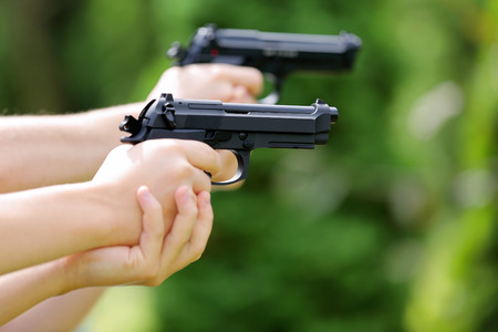Young boys practice shooting guns on outdoor