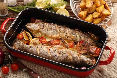 Gebackener Fisch mit Gemüse und Kartoffeln in Pfanne auf Holzuntergrund Standard-Bild - 81669538