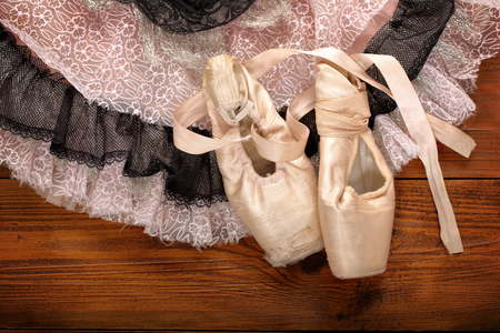 pointes: Used pointes female ballet shoes with skirt tutu on wooden background