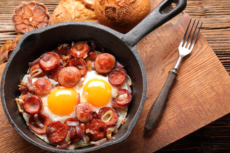 Cooked egg and sausages on frying pan Stock Photo