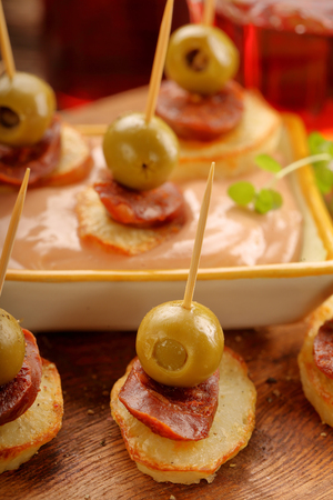 Baked potatoes spanish snack with sausage chorizo and green olive tapas appetizer Stock Photo
