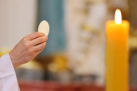 El sacerdote da la sagrada comunión al lugar fiel y vacío para el texto Foto de archivo - 85363540