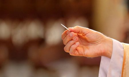 Priest gives holy communion to faithful and empty place for text