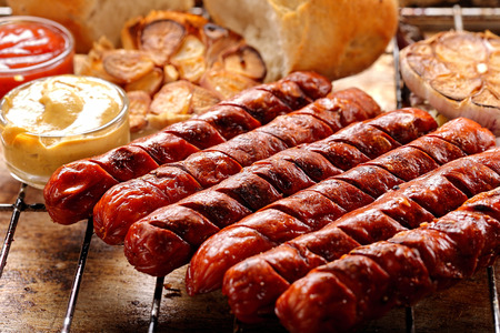 Grilled sausages with sauce ketchup and mustard on metal grate