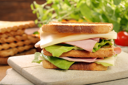 Fresh sandwich with ham and cheese on wooden background